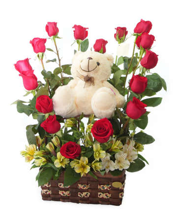 Floral gift arrangement made with red roses with long stems inside a brown pot with teddy bear on white background Stock Photo