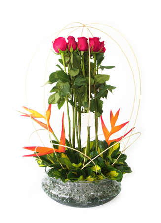 Floral gift arrangement made with red roses with long stems inside a glass pot on white background