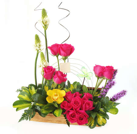 Floral gift arrangement made with red roses with long stems and yellow flowers inside a wooden pot on white background