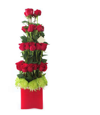 Floral gift arrangement made with red roses with long stems inside a red pot on white background