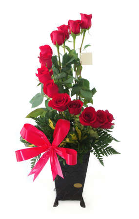Floral gift arrangement made with red roses with long stems inside a black pot with red bow on white background