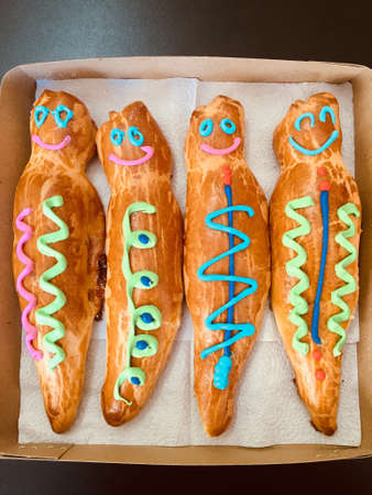 GUAGUA DE PAN - Bread boy in Spanish language - Group of breads decorated with colored lines inside a cardboard box. This is a traditional meal in Ecuador for the day of the dead saints