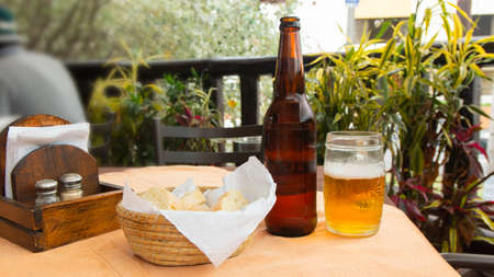 Dark glass beer bottle with a glass mug with lager, a basket of bread on a wooden table with a background of unfocused plants