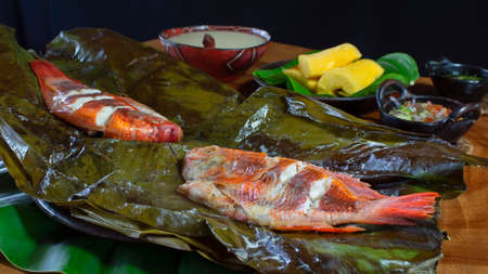 Dishes with fish Maitos, typical food of the Ecuadorian Amazon, accompanied with cassava, cooked banana and salad on a rustic wooden table on black background