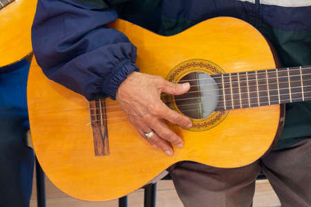 Approach to the hand of an elderly man sitting holding a guitar dressed in a blue shirt with a ring on his finger Archivio Fotografico