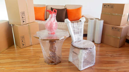 Moving scene with a chair, a vase on a table packed in plastic inside a room with a sofa, plastic rolls and closed cardboard boxes on white background Stockfoto