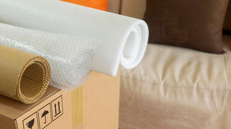 Approach to three rolls of cardboard, foam used to pack things over a cardboard box
