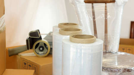 Approach to plastic rolls for packing in the foreground with a plastic wrapped chair, cardboard boxes and adhesive tape in the background Foto de archivo