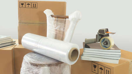 Moving scene with a roll of plastic to pack on a chair wrapped in plastic with closed cardboard boxes, books and masking tape on white background