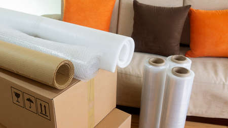 Approach to three rolls of cardboard, foam and used to pack things on a cardboard box a sofa in the background