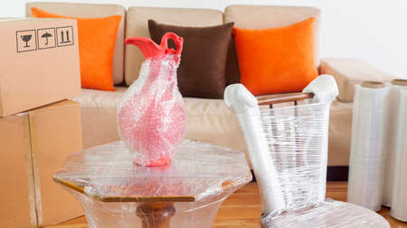 Moving scene with an approach to a chair, a vase on a table packed in plastic inside a room with a sofa, plastic rolls and cardboard boxes closed on white background