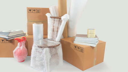 Moving scene with a chair and vase packed in plastic bubble with closed cardboard boxes, books and rolls of plastic and foam to pack on white background