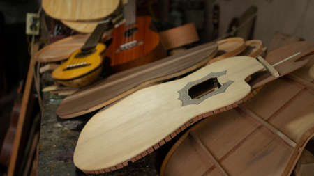 Charango and red wood guitar on a pile of unassembled guitar parts on the carpentry table in a workshop