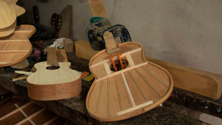 Two wooden guitars in the process of being assembled with presses holding the parts on the carpenter's workbench with gray wall in the background Imagens