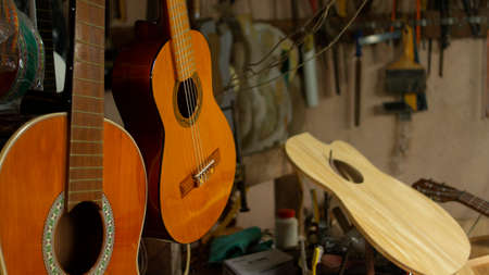 Two hanging wooden guitars and guitar parts on the carpentry table in a workshop with wall full of tools in the background