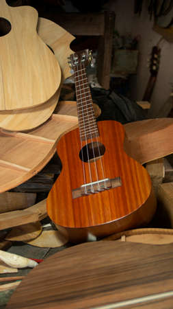 Red wooden guitar on a pile of unassembled guitar parts on the woodworking table in a workshop Imagens