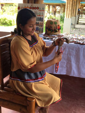 Nueva Loja, Sucumbios / Ecuador - September 2 2020: Indigenous woman of Cofan nationality with yellow dress weaving handicrafts sitting on a chair in her house in the Amazon rainforest
