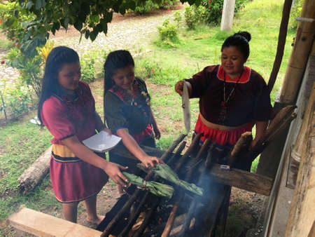 Nueva Loja, Sucumbios / Ecuador - September 2 2020: Group of indigenous women of Cofan nationality cooking maitos outside their house in the middle of the Amazon rainforest Editorial