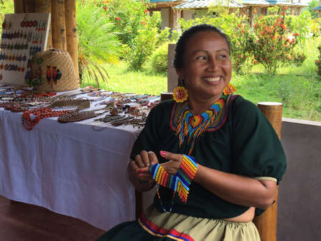 Nueva Loja, Sucumbios / Ecuador - September 2 2020: Indigenous woman of Cofan nationality with green dress smiling while weaving handicrafts sitting on a chair at her home in the Amazon rainforest