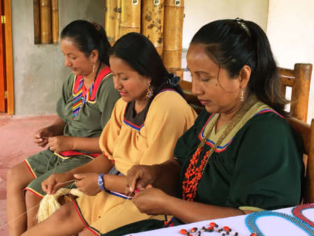 Nueva Loja, Sucumbios / Ecuador - September 2 2020: Group of three indigenous women of Cofan nationality weaving handicrafts in their home in the Amazon rainforest