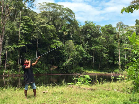 Nueva Loja, Sucumbios / Ecuador - September 2 2020: Young indigenous woman of Cofan nationality hunting with her blowgun in the middle of the Amazon jungle
