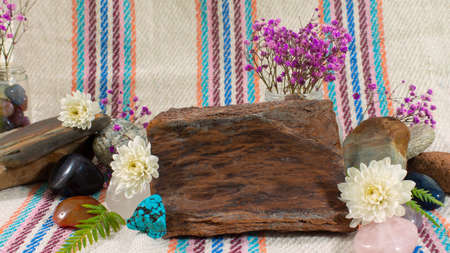 Composition with two glass bottles with bath salts on wooden table with towels, pink stone, purple flowers and cloth with lines in the background Imagens