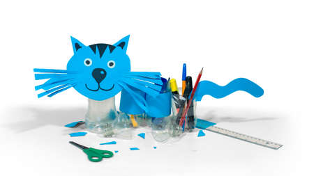 Blue cat made with cardboard and recycled plastic bottles that can be used as pencil holders on table with scissors and ruler on white background Imagens