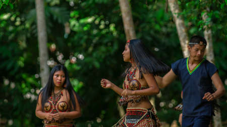 Tena, Napo / Ecuador - October 10 2020: Group of young people dancing with typical costumes of the ethnic groups of the Ecuadorian Amazon in a park