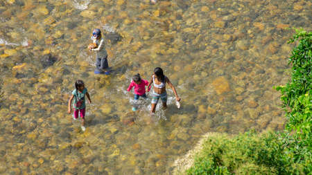 Tena, Napo / Ecuador - October 10 2020: Family bathing in the Napo river during the day in the city of Tena seen from above
