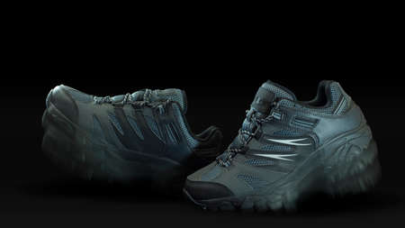 Closeup on a pair of blue gray fabric and leather sports shoes one in front of the other with walking effect on black background