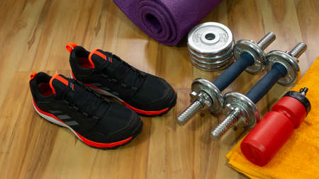 Gym set of pair of black sports shoes, exercise weights, yellow towel and red bottle with water on wooden floor Stock Photo