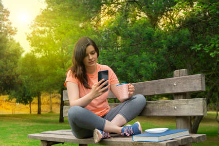 Beautiful young Hispanic woman sitting on a wooden bench in the park dressed in sportswear with a cup of coffee in her hand reading a message on her smartphone with green trees background