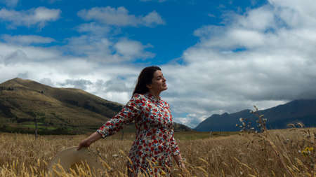 Happy young woman in floral dress walking in the middle of a wheat field with a hat in hand on a cloudy day with blue sky and mountains in the background