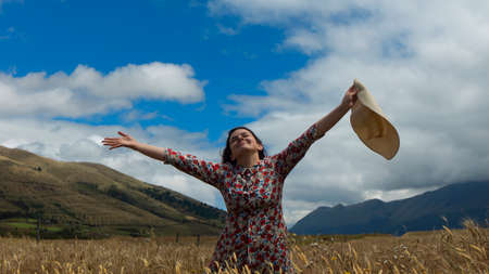 Happy young woman in floral dress with raised arms looking up at the sky with a hat in her hand in the middle of a wheat field on a cloudy day with blue sky and mountains in the background