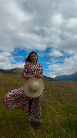 Happy young woman in floral dress holding her hat with her right hand walking alone in the middle of a wheat field seen from the front on a cloudy day with blue sky and mountains in the background Фото со стока