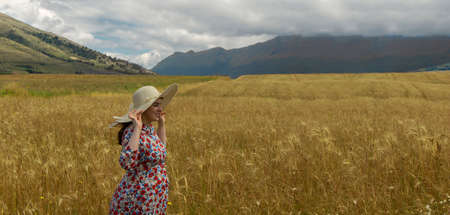 Happy young woman in floral dress holding her hat with her hands walking alone in the middle of a wheat field on a cloudy day with blue sky and mountains in the background Фото со стока