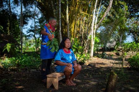 Nueva Loja, Sucumbios / Ecuador - September 2 2020: Elderly indigenous shaman of Cofan nationality performing healing ritual to a Cofan woman in the Amazon rainforest
