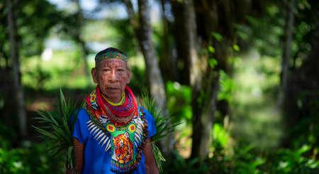 Nueva Loja, Sucumbios / Ecuador - September 2 2020: Close up of an elderly shaman of the Cofan nationality walking in the middle of the Amazon jungle Редакционное