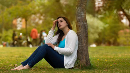 Portrait of beautiful young Hispanic woman sitting under a tree in the middle of a park with a pensive attitude against a background of unfocused trees during the day