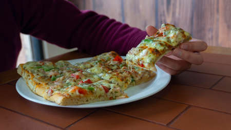 Woman's hand taking a rectangular piece of square pizza with ham, green pepper, tomato, olives and cheese from a white plate on a wooden table Фото со стока