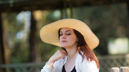 Portrait of beautiful long-haired Hispanic young woman wearing a hat sitting on a park bench with a pensive attitude against a background of unfocused green trees during sunset Фото со стока