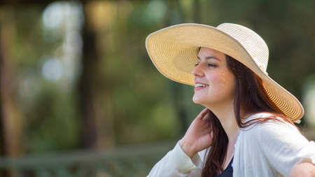 Portrait of beautiful young Hispanic woman with long hair with a hat very cheerful sitting on a park bench against a background of unfocused green trees during sunset