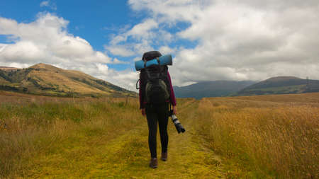 Beautiful Hispanic female explorer seen from behind with backpack walking with a camera in hand in the middle of a sown field on a cloudy morning