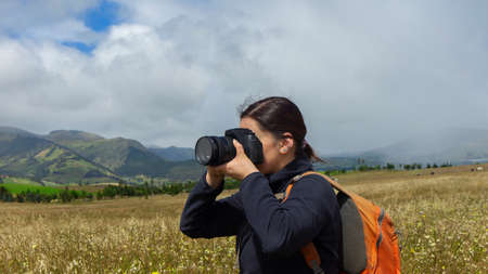 Close up of a beautiful Hispanic female scout with a backpack taking a picture in the middle of a sown field on a cloudy morning