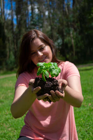 Beautiful young Hispanic woman holding a small plant in her field hands before being planted in a green field surrounded by trees during the morning