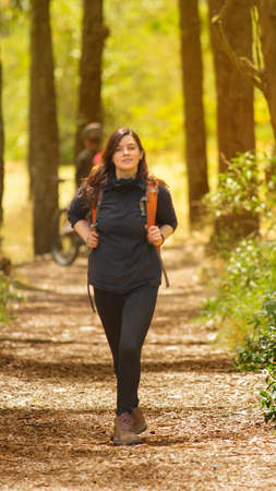 Beautiful Hispanic woman dressed in black with backpack walking alone on a forest path during the morning Фото со стока