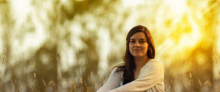 Portrait of beautiful Hispanic young woman with long hair looking at the camera against a background of unfocused trees during sunset with copy space