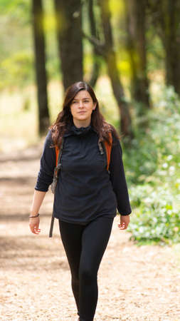 Beautiful Hispanic woman with backpack walking alone on a forest path during the morning