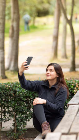 Beautiful young Hispanic woman taking a selfie with her cell phone sitting on a park bench during the morning Фото со стока