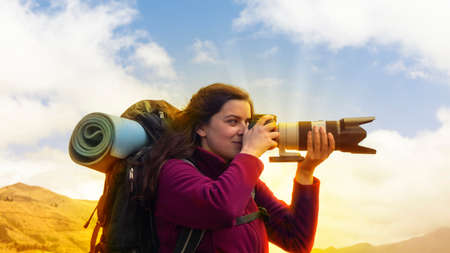 Close up of a beautiful Hispanic female scout with a backpack taking a photo with a telephoto lens on a morning
